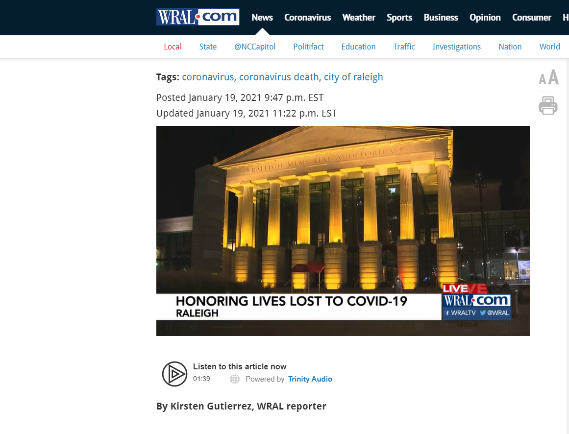 A screenshot of the wral.com news page showing a photo at the top of the raleigh memorial auditorium with amber lights on below that is additional text
