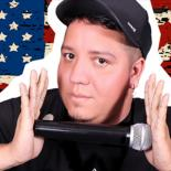 Alan Saladna stands in front of an American flag holding a microphone between both hands