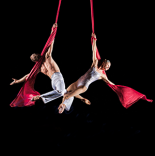 Two acrobats, dressed in all white, are close to each other and hang from red silk ribbons