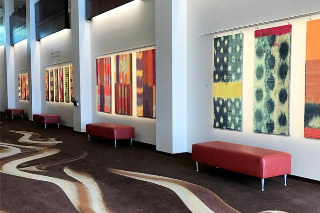 Multiple brightly colored taperstires hang from the walls of the Betty Ray McCain Art Gallery
