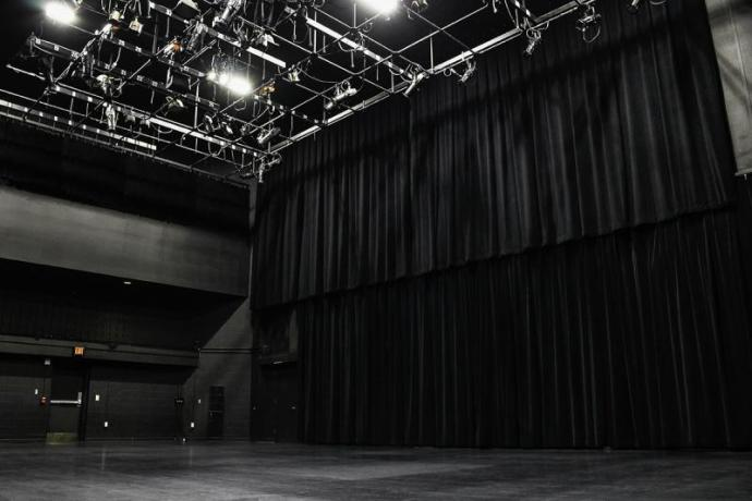 A large black curtain hangs from the ceiling in front of a blank stage in the black box Kennedy Theatre