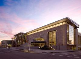 Exterior photo of the Raleigh Convention Center with a pink and purple sunset in the background