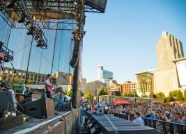 The left side of the photo shows a band on stage performing at the red hat amphitheater and the right side shows the raleigh skyline buildings and the audience
