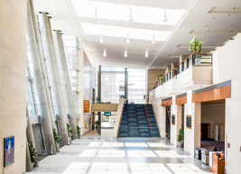 Photo of the main lobby of the raleigh convention center. The lobby is empty and stairs are in the background