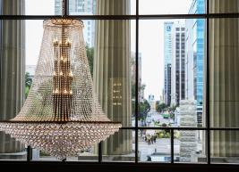 A photo of a chandelier in the Raleigh Memorial lobby looking out to the Raleigh skyline through the upper level windows