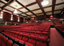 Interior photo of the red seats in Raleigh Memorial Auditorium. Two large chandeliers are visible at the top of the photo.