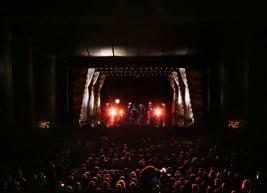 a view of the stage of Raleigh Memorial Auditorium from the audience showing a band on stage and two bright lights