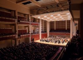 of view of the stage of Meymandi Concert Hall from the upper balcony boxes showing guests in seats and the NC Symphony on stage
