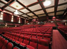 a view of the red seats of Raleigh Memorial Auditorium showing chandeliers