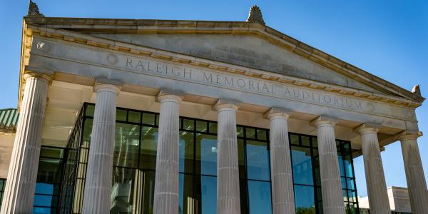The facade of the gothic columns sit in front of the glass at the entryway of Raleigh Memorial Auditorium